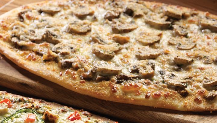 Crujiente masa delgada cubierta con nuestro pesto de champiñones hecho con champiñones portobello, shiitake y porcini. Ligeramente espolvoreado con pan molido, queso mozzarella y champiñones marinados en rebanadas.