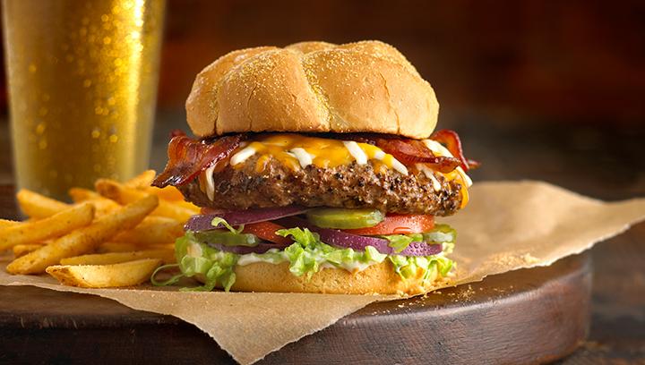 Nuestra Boston's Burger con una mezcla de quesos cheddar y mozzarella, y tocino ahumado. Servida con lechuga, tomates, cebolla roja, pepinillos y mayonesa en un pan Kaiser tostado.