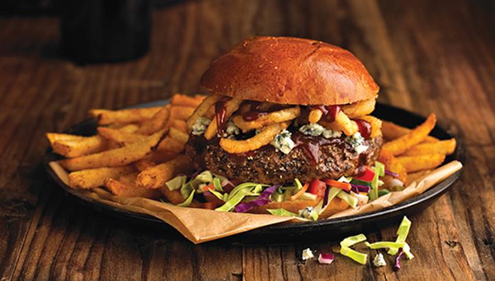 Nuestra jugosa hamburguesa Angus cubierta con crujientes tiras de cebolla y blue cheese, bañados con salsa BBQ, acompañada de ensalada de col tipo Baja.