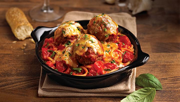 Una cama de pasta bucatini y albóndigas cubierta en salsa pomodoro, tomates frescos, ajo y albahaca, horneada con quesos cheddar y mozzarella.