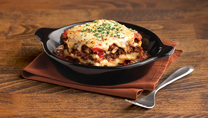 Capas de pasta con salsa de carne, carne con especias, quesos fontina, mozzarella, ricotta y parmesano, aderezado con un ligero toque de vino tinto.